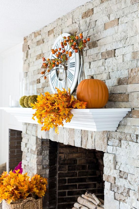 a rustic mantel with fall elaves, moss balls, pumpkins and fruits on the branches is suitable for both fall and Thanksgiving
