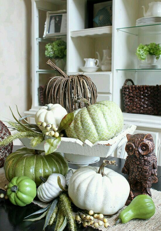 a vintage and rustic centerpiece with faux pumpkins in green and white and of vine is amazing for fall or Thanksgiving decor