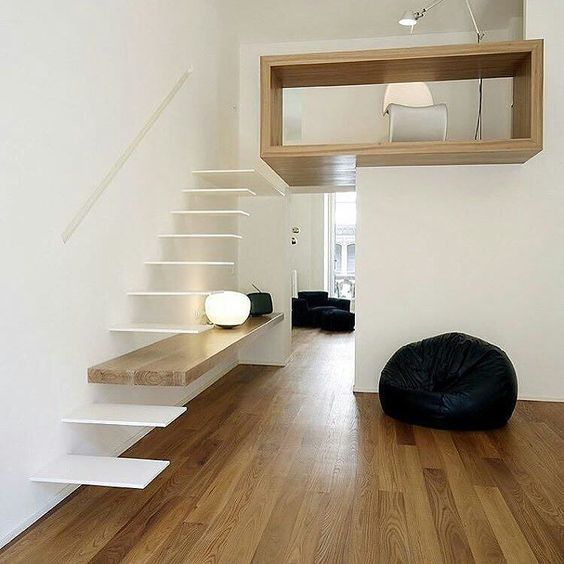 an ultra-minimalist staircase with white floating steps and a shelf integrated into the construction