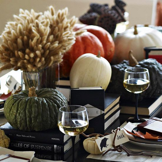 black books and various heirloom pumpkins plus a wheat arrangement in a vase for a chic Halloween centerpiece