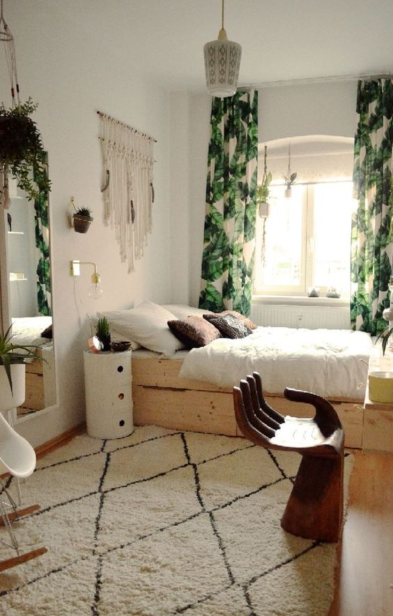 leaf printed curtains dominating in this boho bedroom and a neutral rug that doesn't stand out much