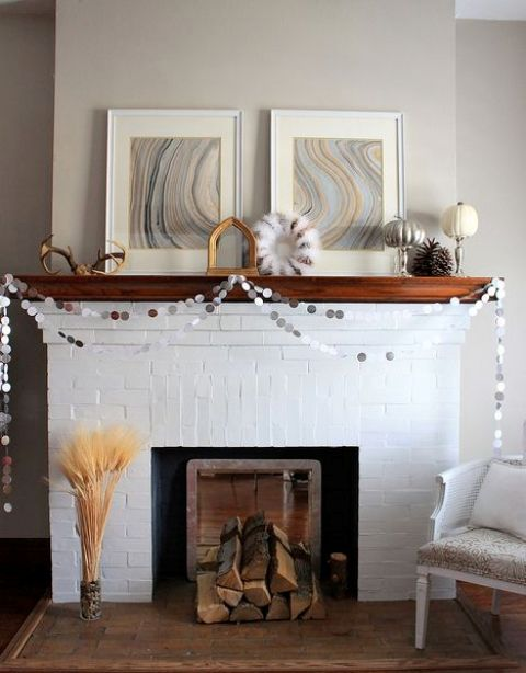 a colorful banner, a cotton wreath, antlers, a pumpkin, firewood and some wheat next to the fireplace