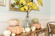 15 a cozy Thanksgiving console with fabric baskets, heirloom pumpkins and fall leaf branches in a vase