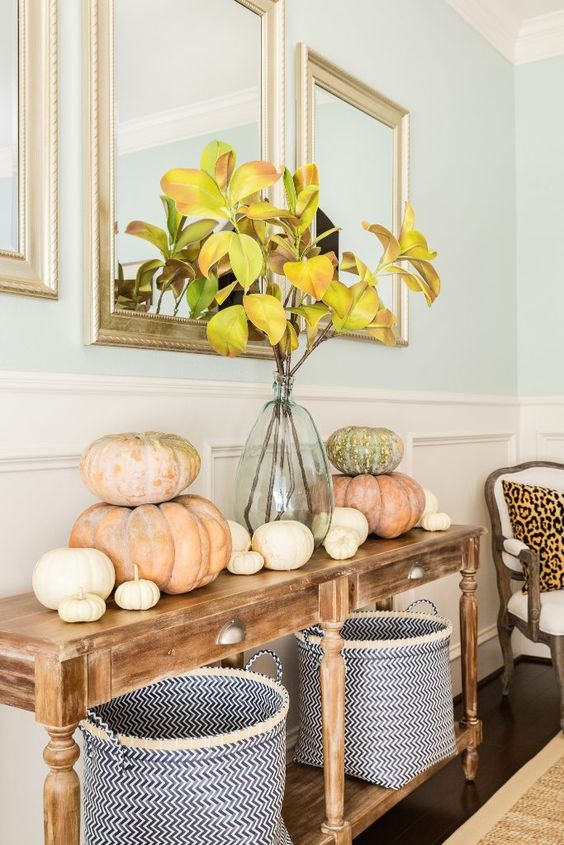 a cozy Thanksgiving console with fabric baskets, heirloom pumpkins and fall leaf branches in a vase