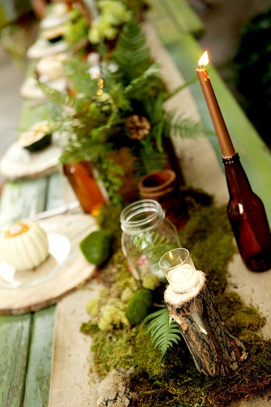 a table runner of moss, foliage and moss balls for a Thanksgiving table setting
