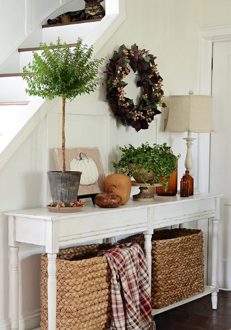 a vintage console with baskets, faux pumpkins, potted plants and a wreath of fake leaves and berries