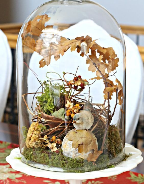 a beautiful fall display with moss, fall leaves, berries,  fake bird and a fake nest of twigs for a rutic feel