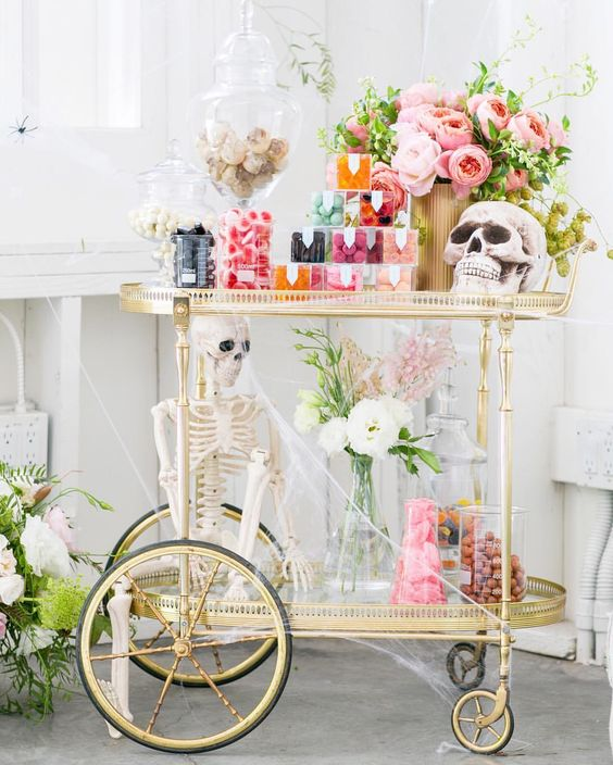 a chic vintage Halloween bar cart with skeletons,colorful candies and a bright pink peony centerpiece