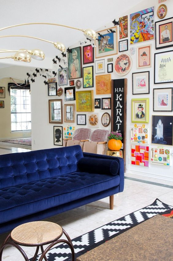 a colorful space with a bold gallery wall with various artworks and mirrors