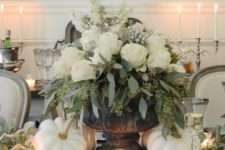16 a luxurious Thanksgiving centerpiece with a vintage urn, seeded eucalyptus, white roses, berries and white pumpkins around
