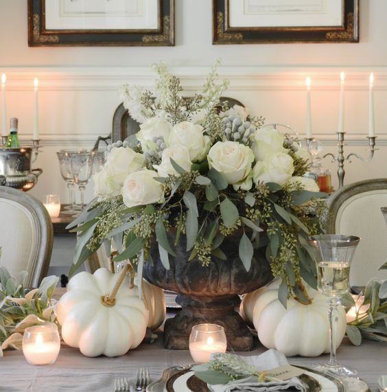 a luxurious Thanksgiving centerpiece with a vintage urn, seeded eucalyptus, white roses, berries and white pumpkins around