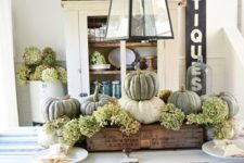 16 a rustic Thanksgiving centerpiece of white and green pumpkins and green hydrangeas in an industrial crate