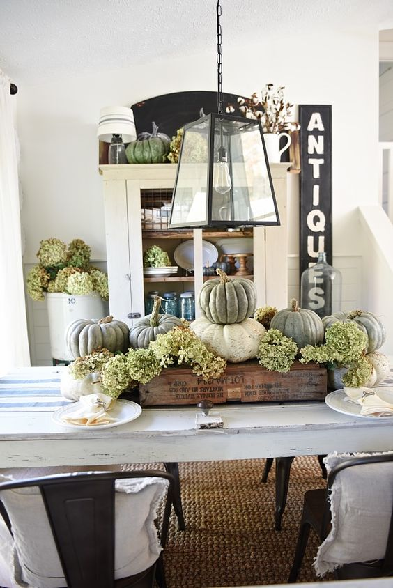 a rustic Thanksgiving centerpiece of white and green pumpkins and green hydrangeas in an industrial crate