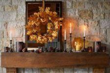 16 a rustic fall mantel with pinecones, candles, a fall leaf wreath for a cozy and comfy feel
