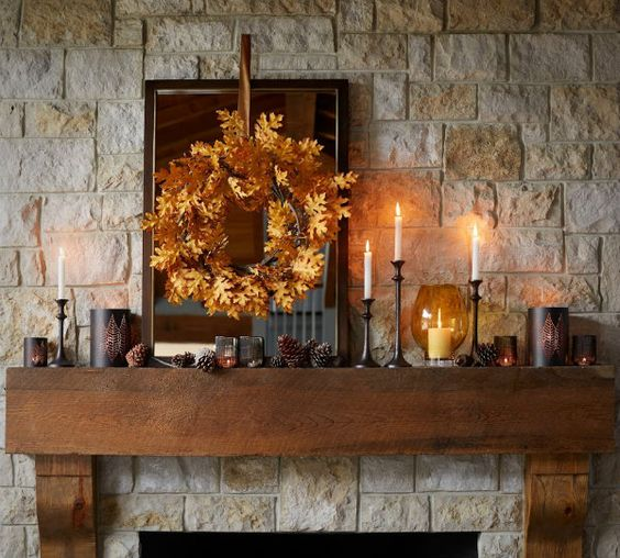 a rustic fall mantel with pinecones, candles, a fall leaf wreath for a cozy and comfy feel