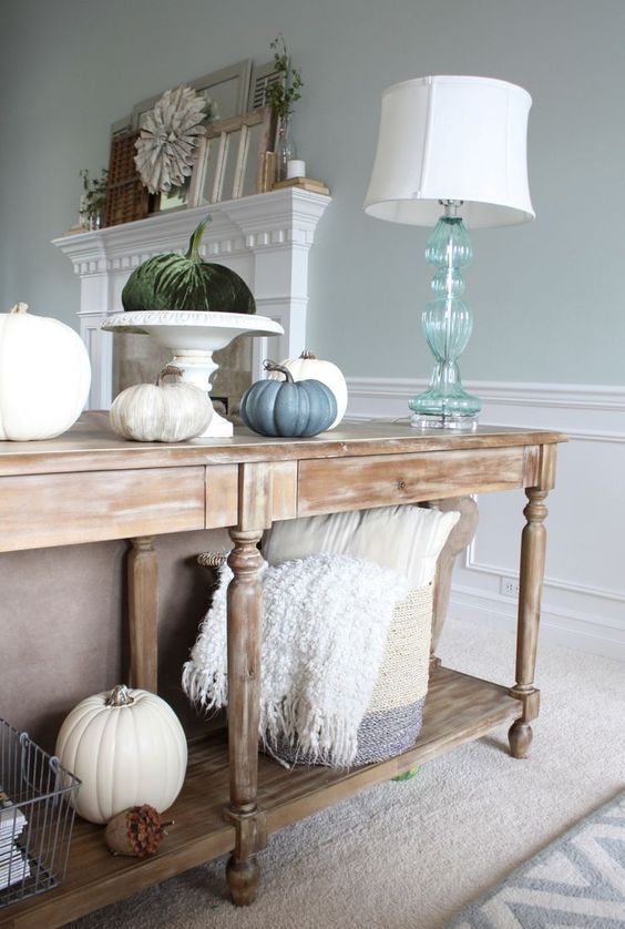 a vintage console with faux pumpkins including fabric ones and a basket with pillows and blankets