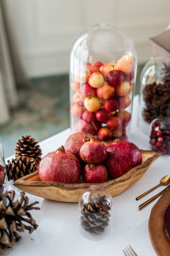 a cloche filled with little fall apples and a centerpiece of a wooden bowl with pomegranates plus pinecones