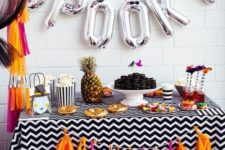 17 a colorful candy bar with a bright tassel garland and silver letter balloons plus a pineapple for a tropical feel