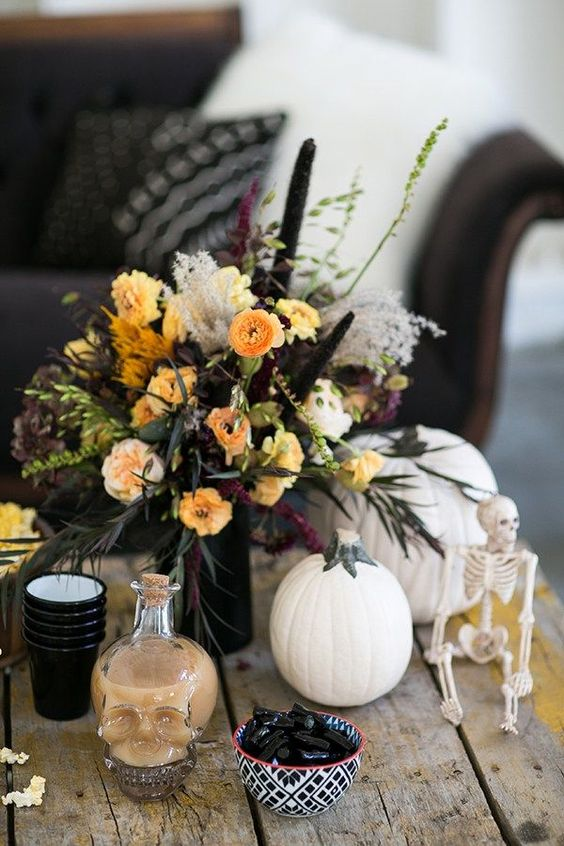 a lush floral centerpiece with fall blooms, greenery and black touches is what you need for a chic look