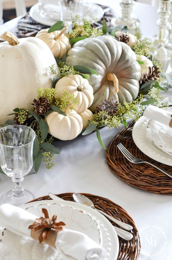 a natural fall centerpiece of a tray, seeded eucalyptus, heirloom pumpkins and pinecones for a rustic feel