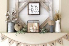 17 a rustic fall or Thanksgiving mantel with cotton, fabric pumpkins, herbs and a sign in a frame