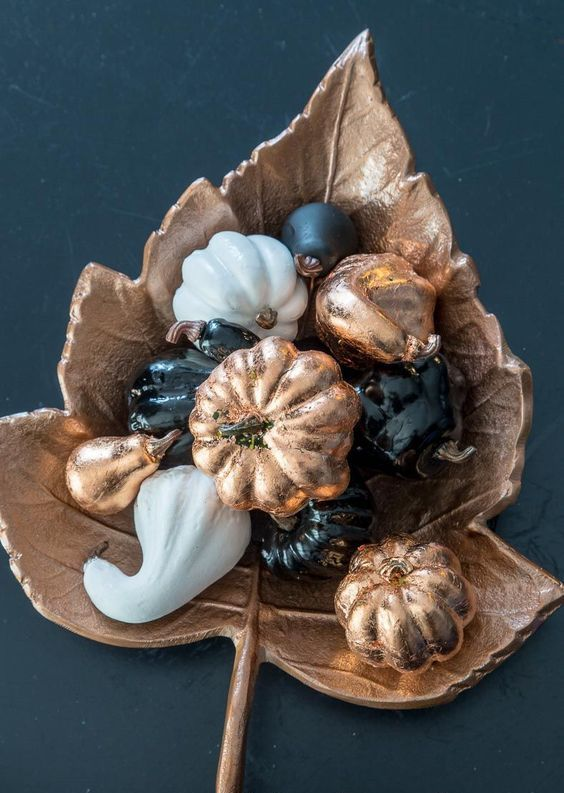 a whimsy fall centerpiece of a copper leaf and black, white and copper faux vegetables for Thanksgiving