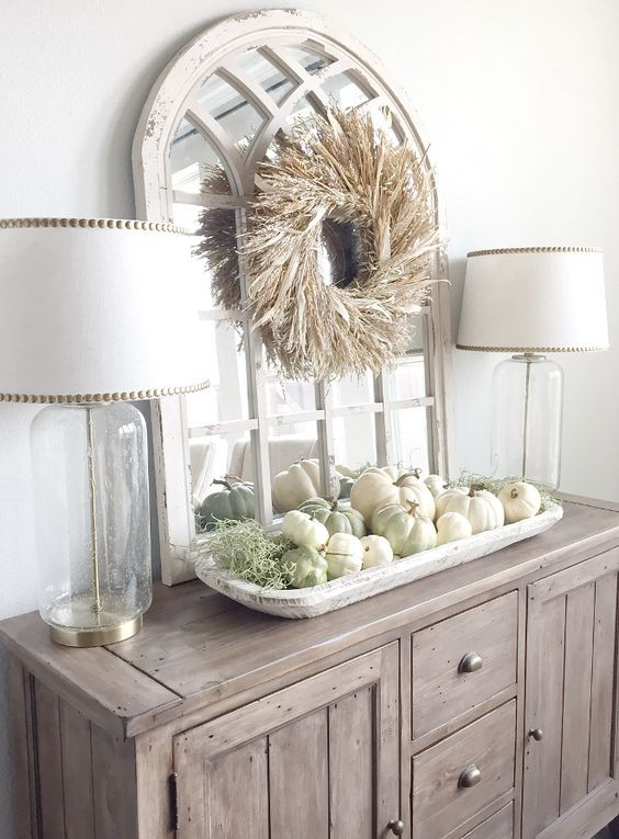 a wooden farmhouse buffet with a whitewashed tray with pumpkins and greenery and a husk wreath over it
