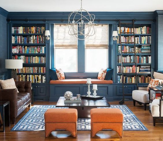 a colorful interior in blue and orange with lots of bookshelves that frame the window