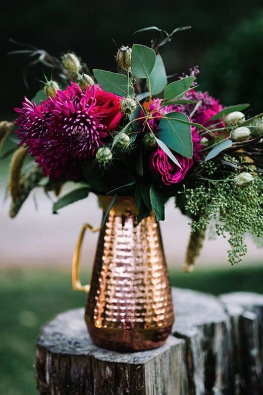 a copper pitcher with purple dahlias and fresh greenery for a bright Thanksgiving centerpiece