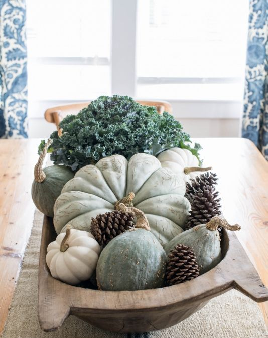 a natural Thanksgiving centerpiece of a bread bowl, pinecones, heirloom pumpkins, gourds and fresh veggies
