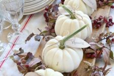 18 a natural rustic centerpiece of a cutting board, white pumpkins and berries for Thanksgiving