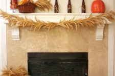 18 a rustic mantel with wheat, baskets with pumpkins and herbs and fruits in a glass jar