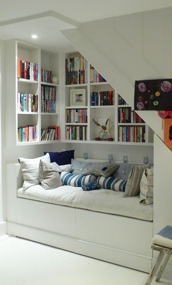 an under the stairs nook for reading, with bookshelves and a large upholstered bench to enjoy