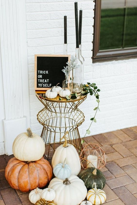 a boho chic outdoor display with a metlalic table, black candles, heirloom pumpkins, greenery and a sign