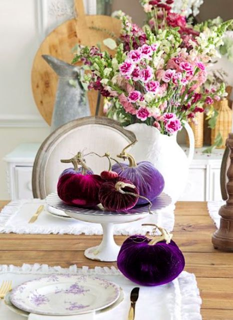 a bright purple and fuchsia velvet pumpkin centerpiece with a pink floral arrangement
