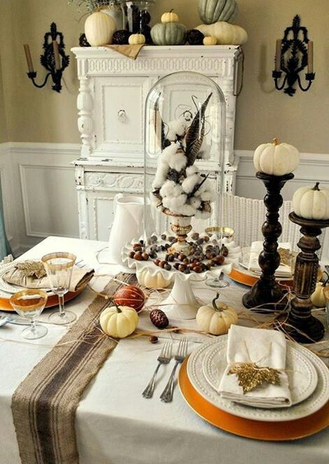 a cloche with nuts, a vintage urn with cotton and feathers plus pumpkins on the table for a vintage tablescape
