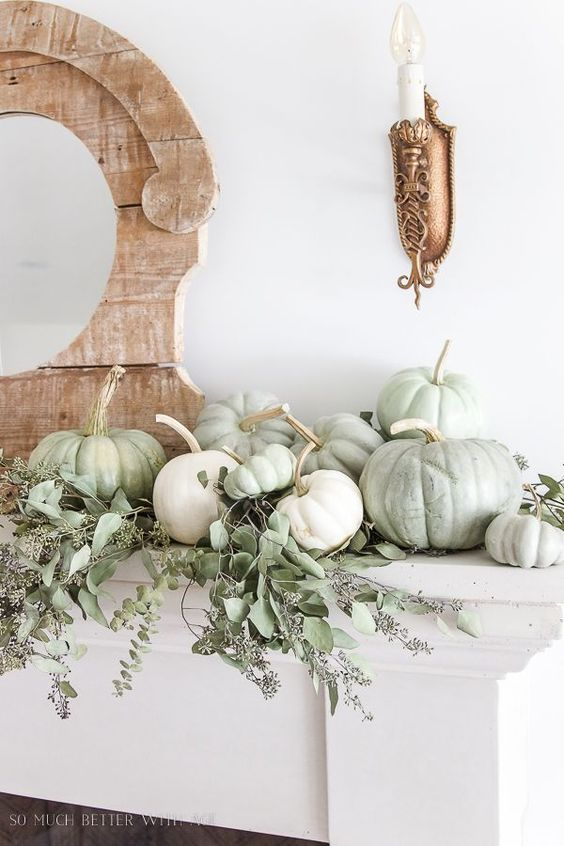 a neutral fall mantel with light green and white pumpkins plus seeded eucalyptus is great for Thanksgiving