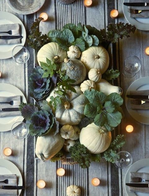 a rustic harvest Thanksgiving centerpiece with white and green pumpkins, various kinds of cabbage and candles around