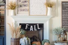 20 a couple of signs and wheat on the mantel and heirloom pumpkins in a tray plus dried herbs in rustic containers