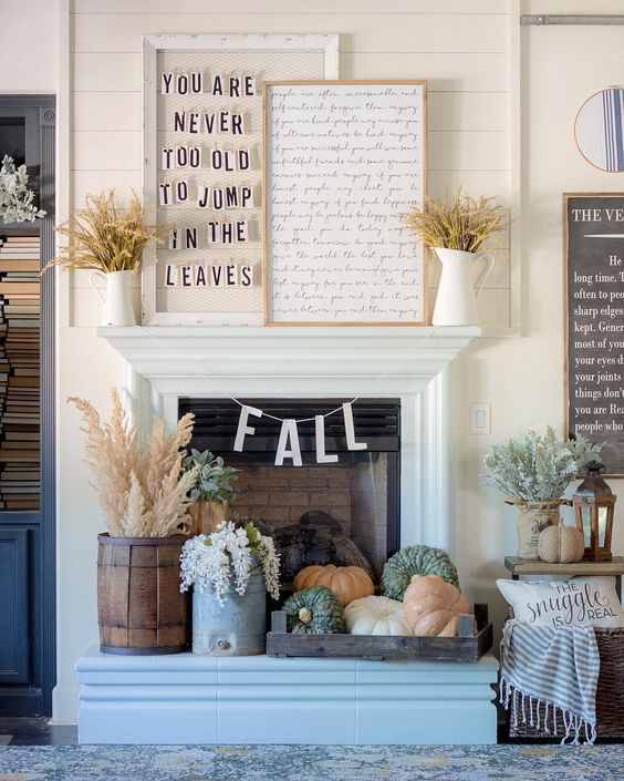 a couple of signs and wheat on the mantel and heirloom pumpkins in a tray plus dried herbs in rustic containers