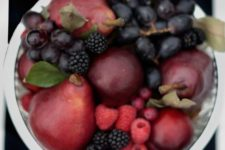 20 a jewel tone centerpiece of a silver bowl, burgundy pears, dark grapes and black berries to highlight the harvest time