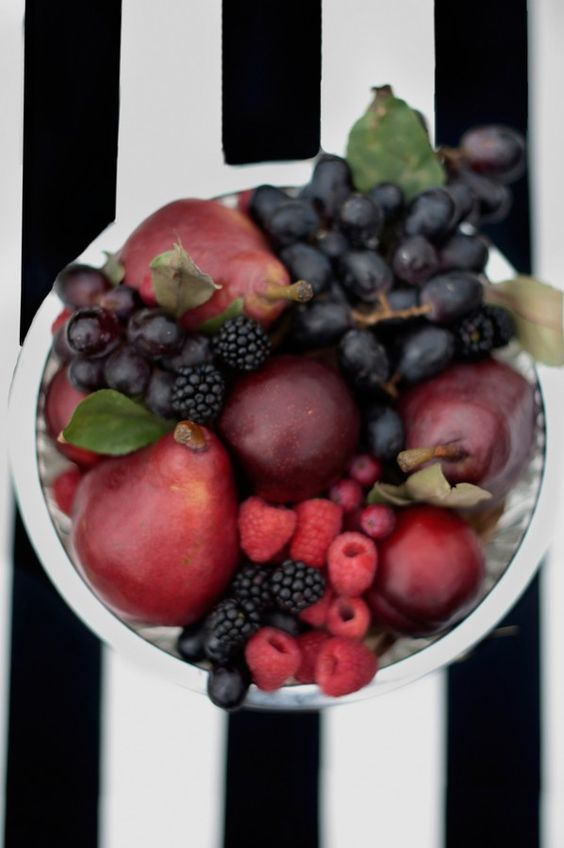 a jewel tone centerpiece of a silver bowl, burgundy pears, dark grapes and black berries to highlight the harvest time