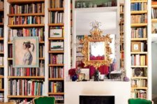 20 a maximalist space with lots of books by the fireplace and colorful furniture and metallics