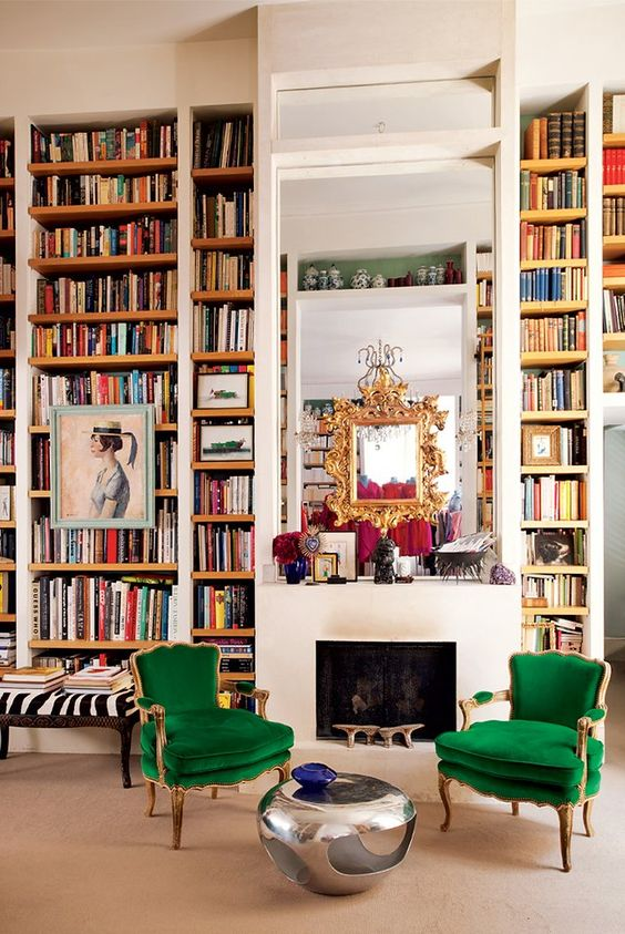 a maximalist space with lots of books by the fireplace and colorful furniture and metallics