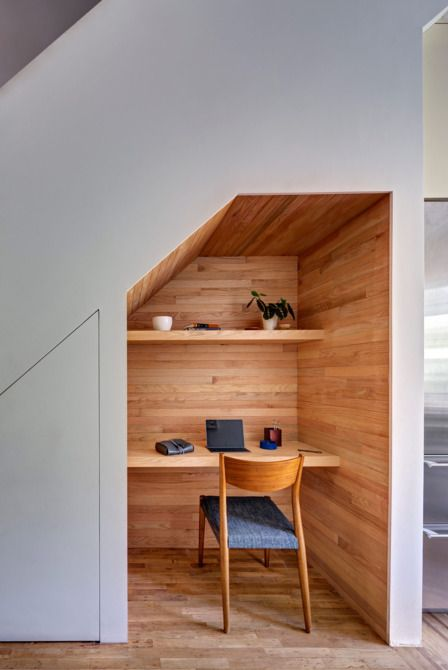 a small home office built in under the stairs and all clad with wood for a cozy feel
