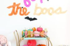 20 a super bright bar cart filled with colorful pumpkins and paper balls, colorful barware and with letters above