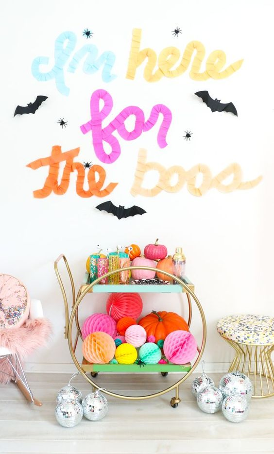a super bright bar cart filled with colorful pumpkins and paper balls, colorful barware and with letters above