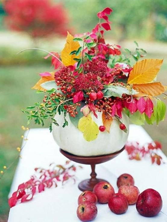 a Thanksgiving centerpiece made of a wooden stand, a white pumpkin, orange leaves and hot red berries plus leaves