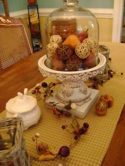 a fall vintage cloche display with fake fruits and twine balls for a rustic and vintage feel