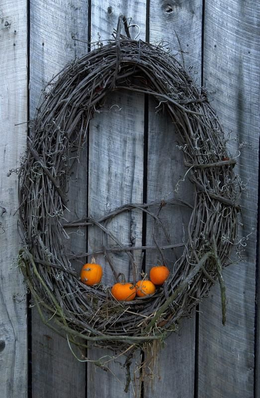 a grapevine wreath with little orange pumpkins is all you need to craft for your front door at Halloween